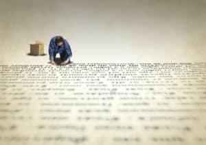 אדם רוכן על בירכיו וכותב